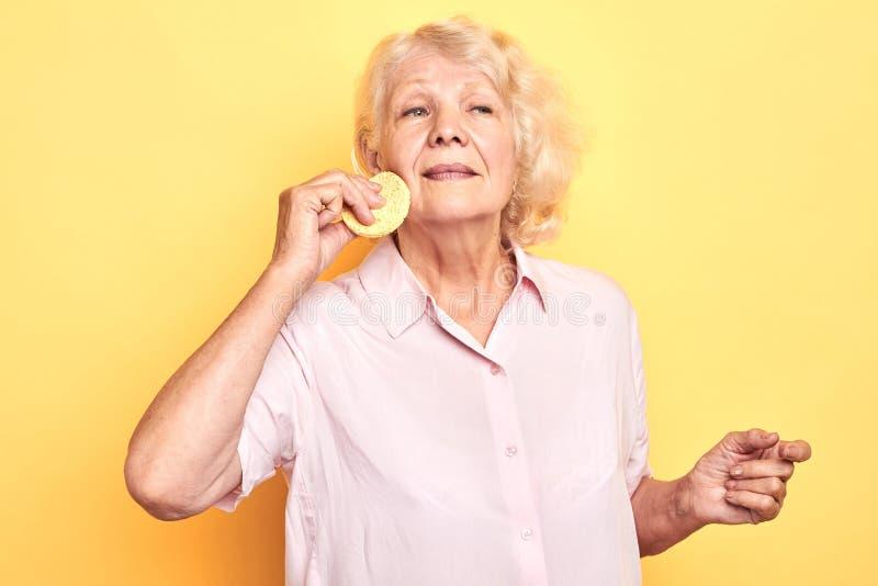 Alte angenehme attraktive Frau, die Schwamm beim Kümmern von  um ihrem Gesicht verwendet stockbild
