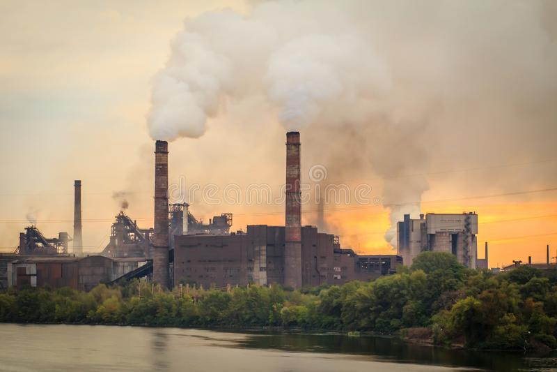 Alte Anlage mit den Schornsteinen, die Rauch in die Atmosphäre durchbrennen stockbilder