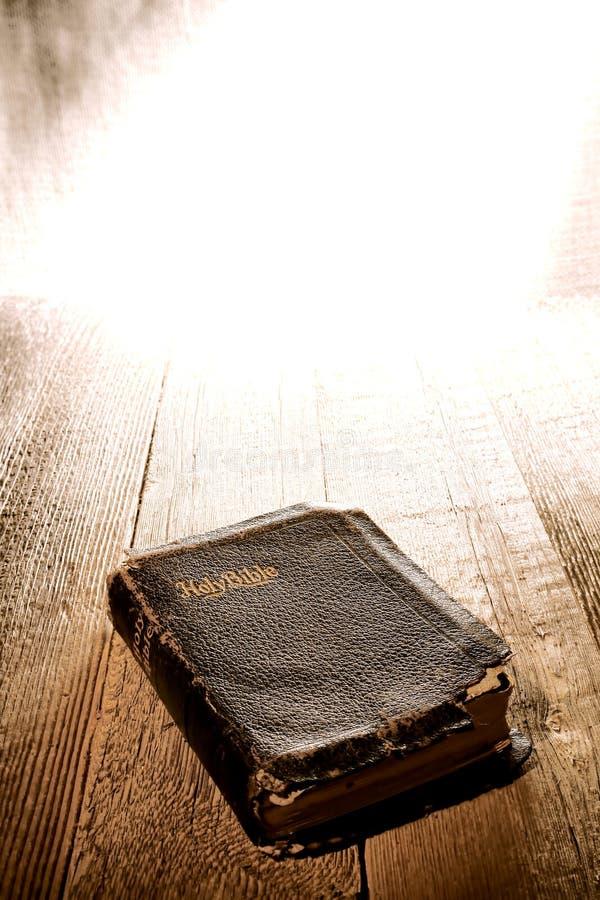 Alte Antike und schädigende heilige Bibel in der göttlichen Leuchte stockbild