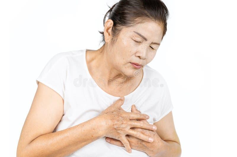 Alte asiatische Frau, die Herzinfarkt lokalisieren lässt auf weißem Hintergrund stockbild