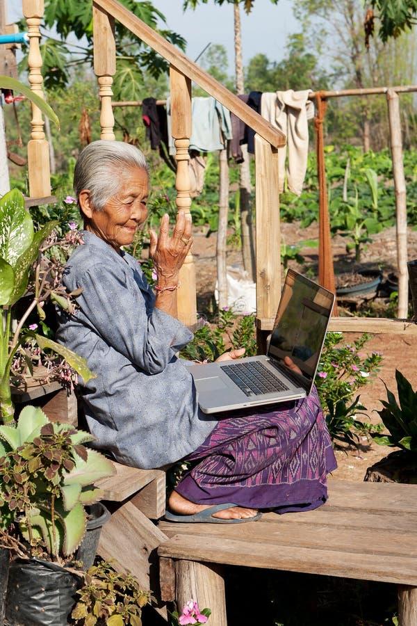 Alte asiatische Frau mit Laptop lizenzfreie stockfotos