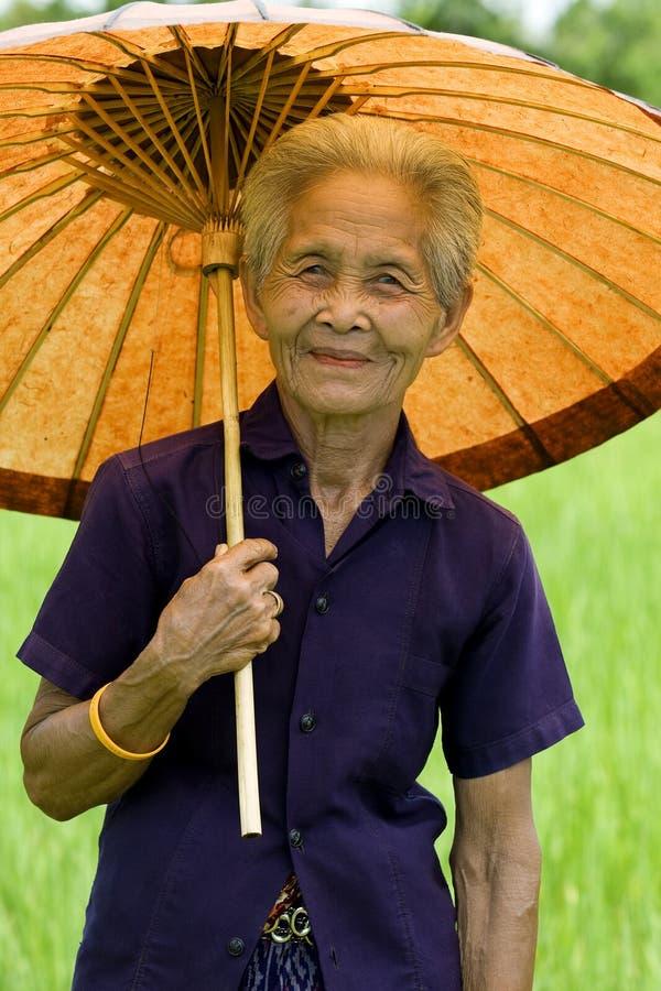 Alte asiatische Frau mit Sonnenschirm lizenzfreie stockbilder