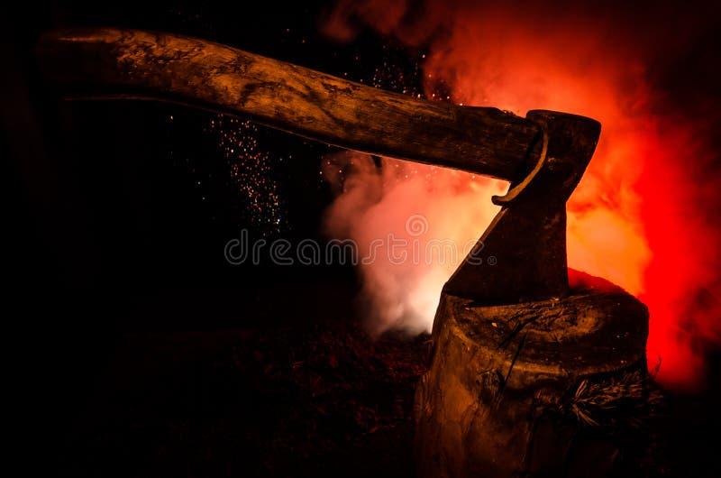Alte Axt befestigt zum Baumstamm auf rotem nebeligem Hintergrund des Horrors Furchtsames Halloween-Thema mit Wahnsinnigemörderwaf lizenzfreie stockfotos