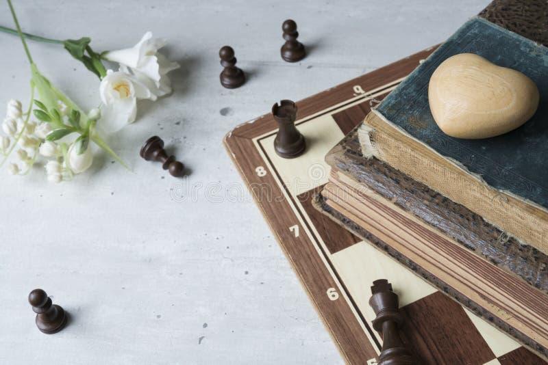 Alte Bücher mit Schachbrett, -herzen und -blumen lizenzfreie stockfotos