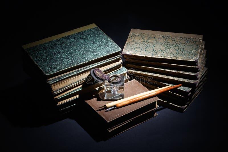 alte Bücher, Papiere, Tintenstift und Inkpot auf Schwarzem lizenzfreie stockfotos