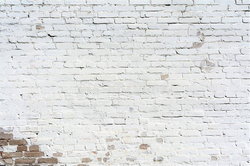 Alte Backsteinmauer der Entlastungsbeschaffenheit gemalt mit weißer Farbe, Schäden auf der Wand von der Wasserführung, abstrakter lizenzfreies stockfoto