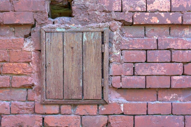 Alte Backsteinmauer mit einem geschlossenen hölzernen Fenster lizenzfreie stockfotografie