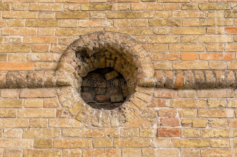 Alte Backsteinmauer mit rundem Embrasure stockbilder