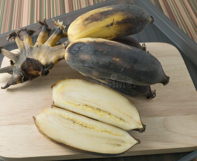 Alte Bananen-Frucht auf einem hölzernen Brett stockfotos
