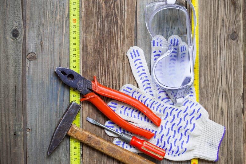 Alte Bauschlosserwerkzeuge, Arbeitshandschuhe, Sicherheitsgläser und messendes Band auf gealterter strukturierter Oberfläche stockfotos