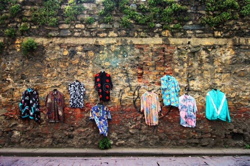 Alte, benutzte Kleidung auf der Wand, Straßenhändler, benutzte Hemden, verziert mit Kleidung lizenzfreies stockbild