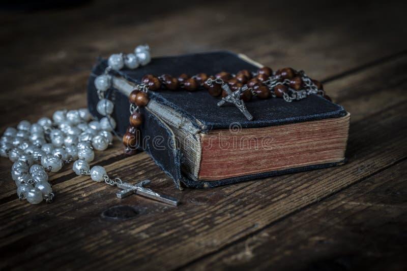 Alte Bibel mit katholischem Rosenbeet auf einer Tabelle stockfotografie