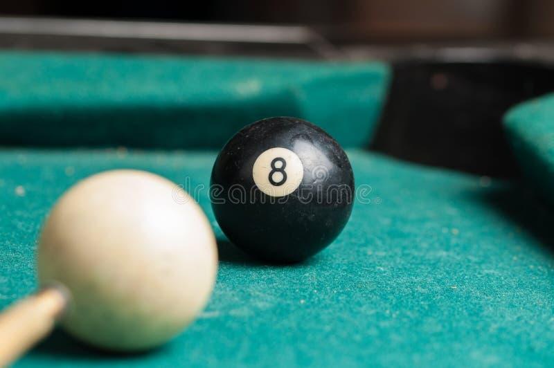 Alte Billardkugel 8 auf einer grünen Tabelle Billardkugeln lokalisiert auf einem grünen Hintergrund lizenzfreies stockfoto