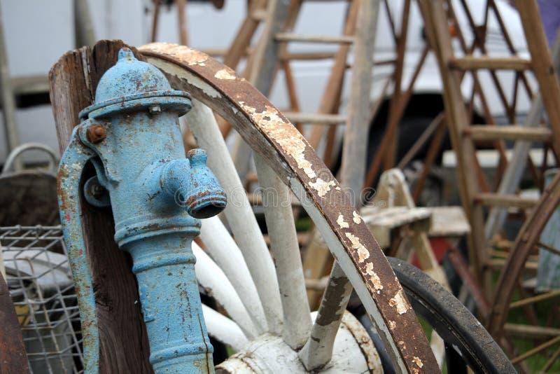 Alte blaue antike Eisenwasserpumpe und großes weißes Wagenrad mit hölzernen Leitern der Weinlese im Hintergrund lizenzfreie stockbilder