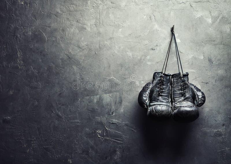 Alte Boxhandschuhe hängen am Nagel auf Beschaffenheitswand lizenzfreies stockbild