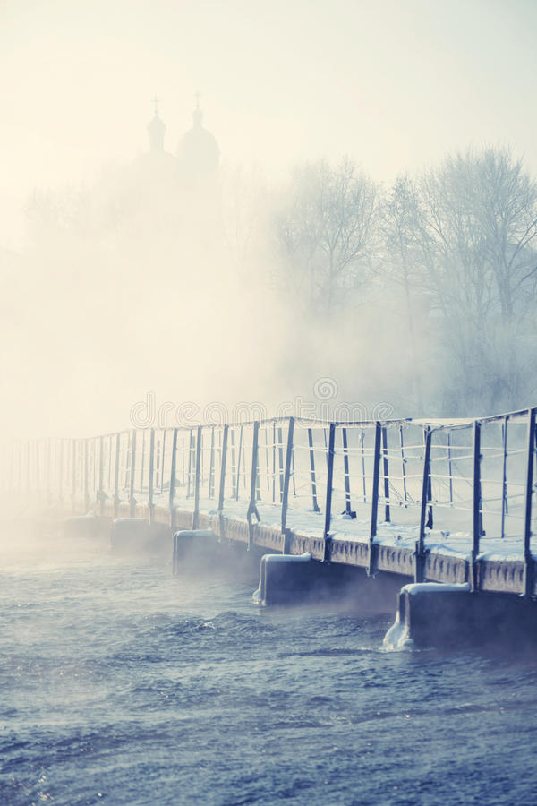 Alte Brücke über dem eisigen Fluss stockbild