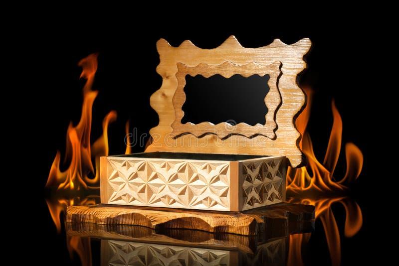 Alte braune hölzerne Schatulle in der Feuerflamme auf schwarzem Hintergrund lizenzfreie stockfotos