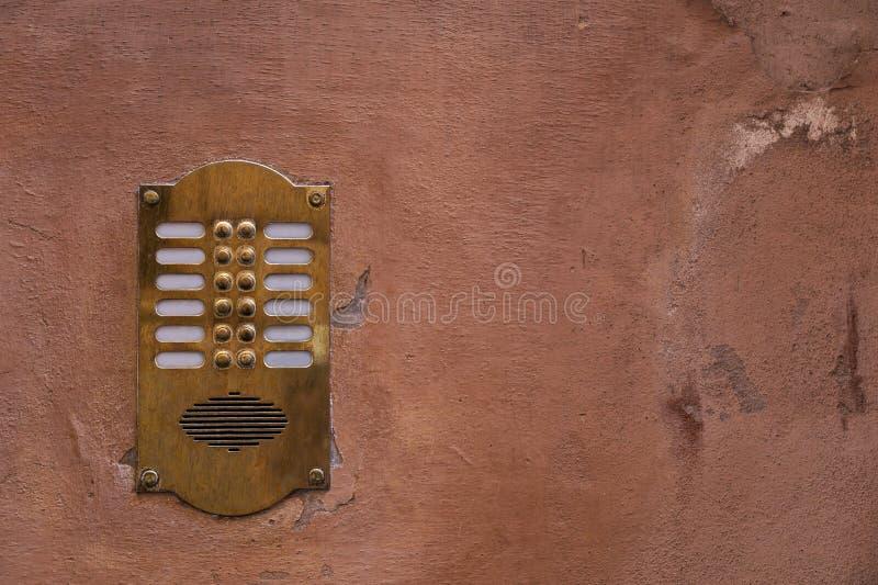 Alte Bronzewechselsprechanlage auf einer alten Wand mit Schalenfarbe lizenzfreie stockfotos