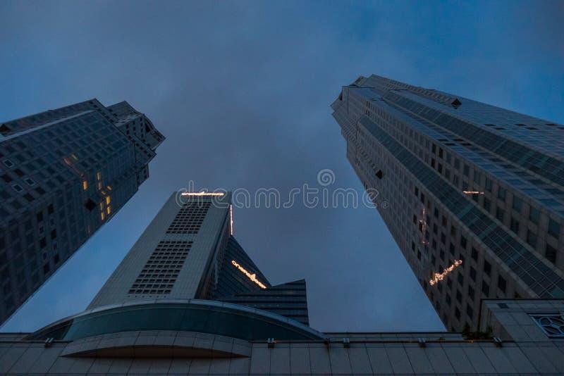 Alte costruzioni di affari del grattacielo contro cielo blu alla notte fotografia stock libera da diritti