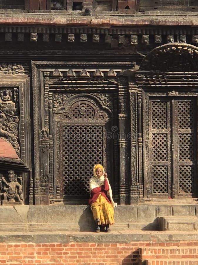 Alte Dame in Bhaktapur Nepal, das auf einer Leiste nahe dem Palast sitzt lizenzfreie stockfotografie