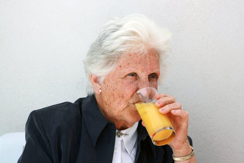 Alte Dame, die Orangensaft trinkt lizenzfreie stockfotografie
