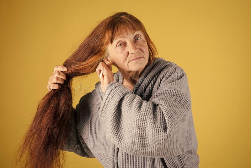Alte Dame mit Haarbürste auf gelbem Hintergrund lizenzfreies stockfoto