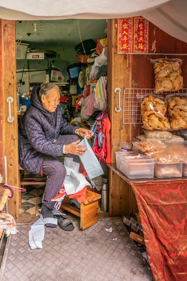 Alte Dame verkauft Trockenfisch aus Bretterbude in Tai O, Hong Kong China heraus lizenzfreies stockbild