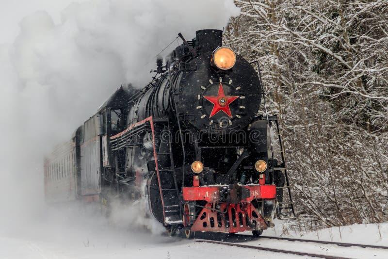 Alte Dampflokomotive Lokomotive durch Schiene im Winter im Wald Region Winterwald-Russlands Leningrad, Gatchina-Bezirk lizenzfreies stockbild