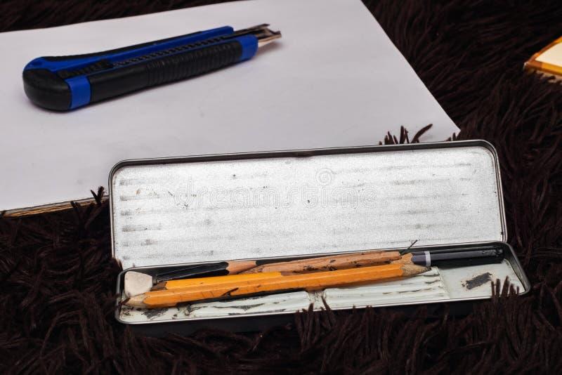 Alte einfache Bleistifte in einem Metallkasten und in einem Blatt lizenzfreie stockfotos
