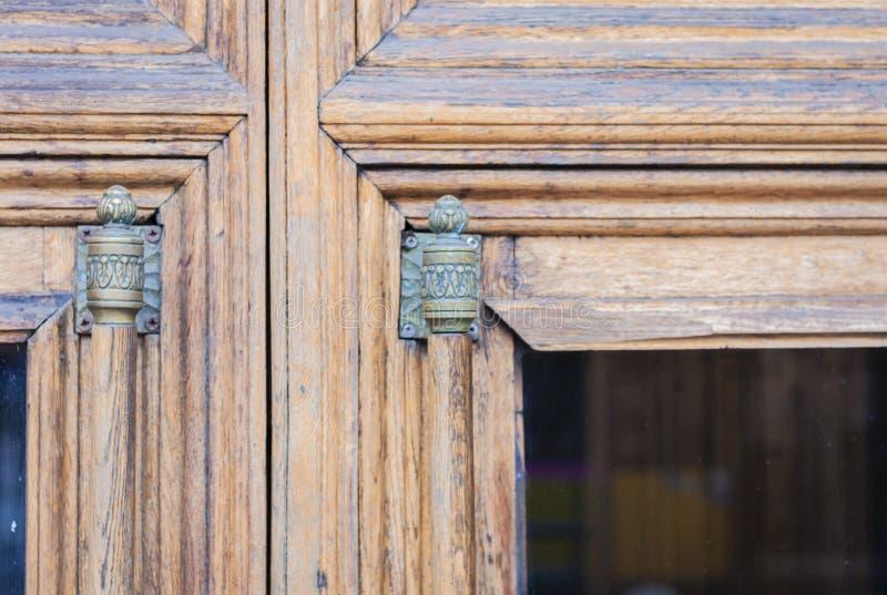 Alte Eingangsholztür mit Glaseinsatz und Weinlesegriff mit einem Bronzeende eines historischen Gebäudes lizenzfreie stockfotos