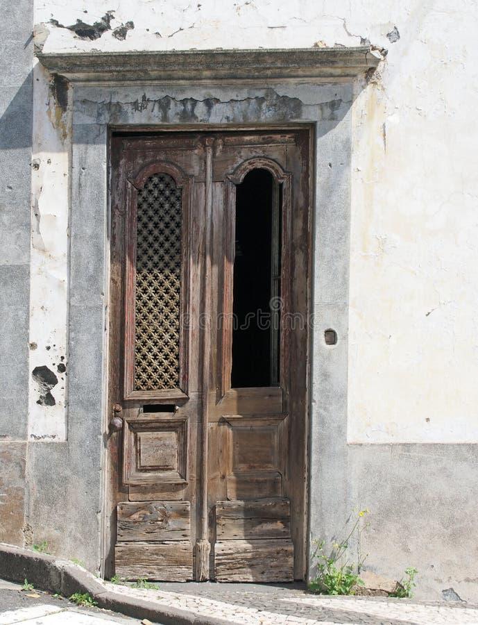 Alte elegante verwitterte aufwändige hölzerne braune Tür mit geschnitzten Platten und Verfehlungsgrill in einem weißen verlassene stockbilder