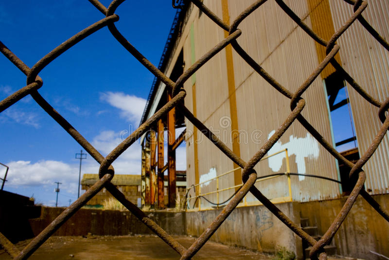 Alte Fabrik hinter Zaun lizenzfreies stockbild