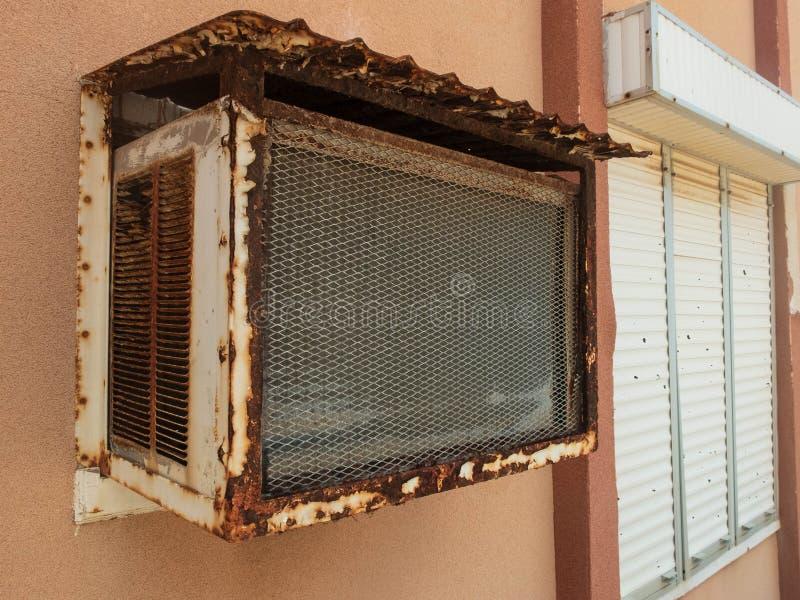 Alte Fensterklimaanlage und Fenster mit geschlossenem rollendem Fensterladen lizenzfreie stockfotografie