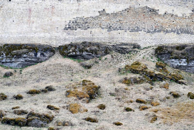 Alte Festungswand, die in den Boden umfasst mit Frühlingsgras und -moos überschreitet stockfoto