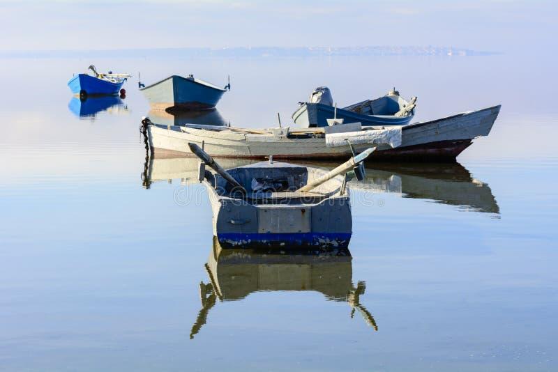 Alte Fischerboote mit hellen Farben an der Dämmerung auf dem See lizenzfreie stockbilder