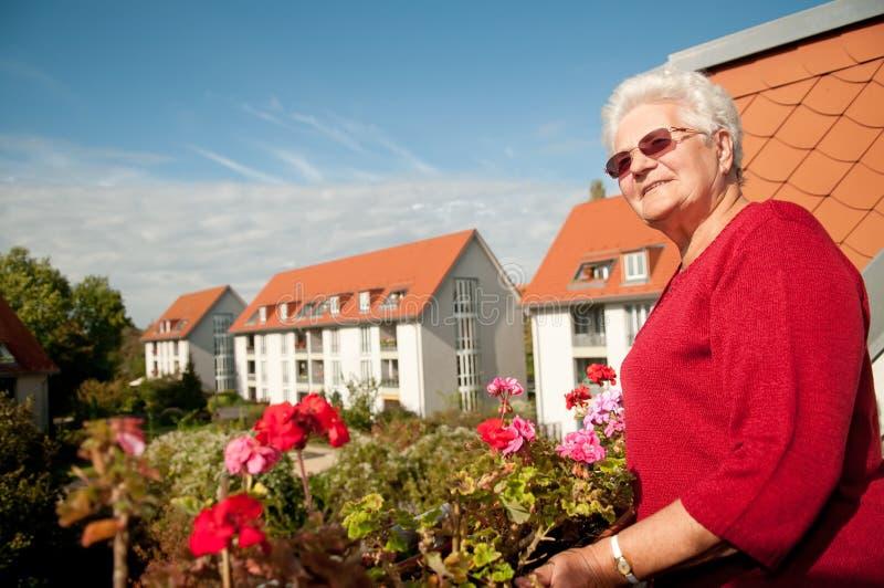 Alte Frau auf dem Balkon lizenzfreie stockfotografie