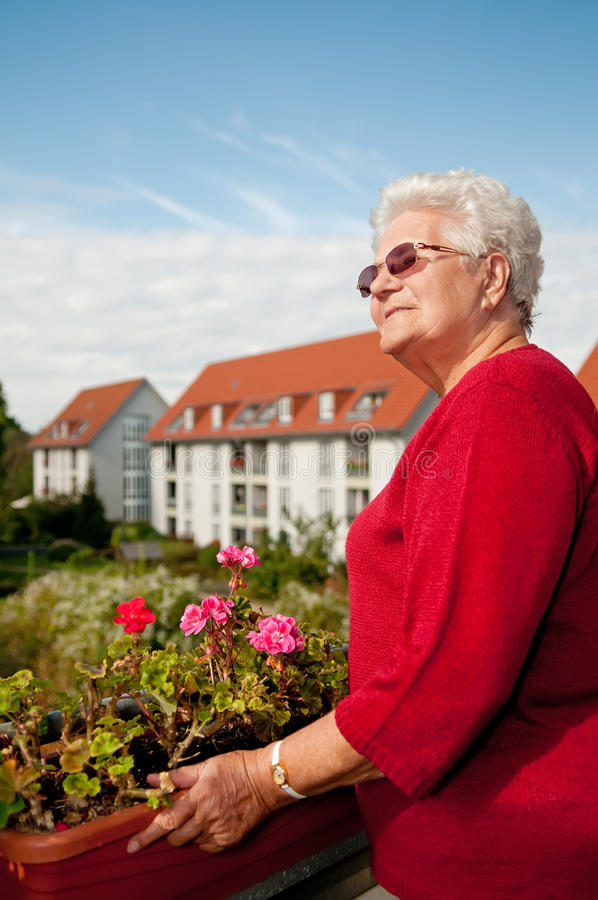 Alte Frau auf dem Balkon stockfotografie