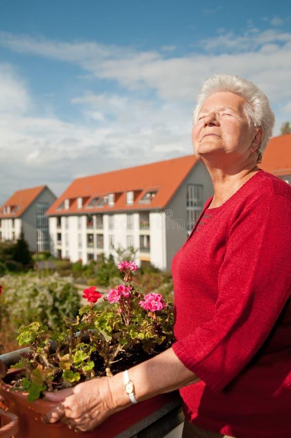 Alte Frau auf dem Balkon lizenzfreies stockbild