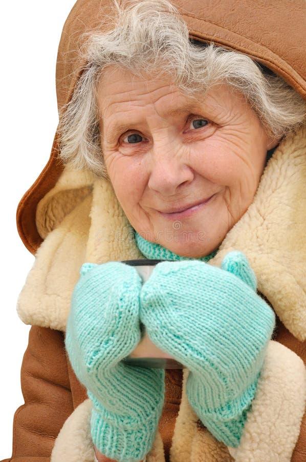 Alte Frau des Porträts mit Becher heißem Tee stockfoto