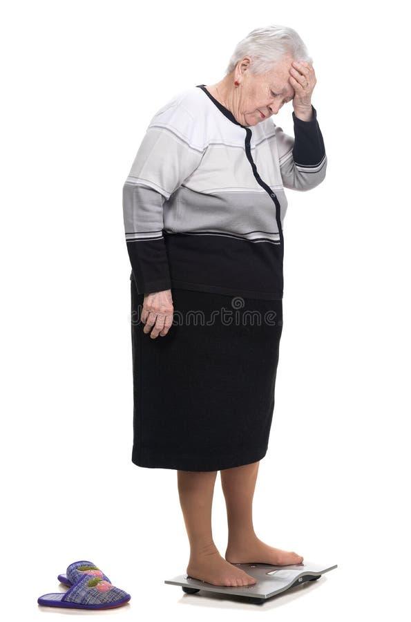 Alte Frau, die auf Badezimmerwaagen steht stockbilder
