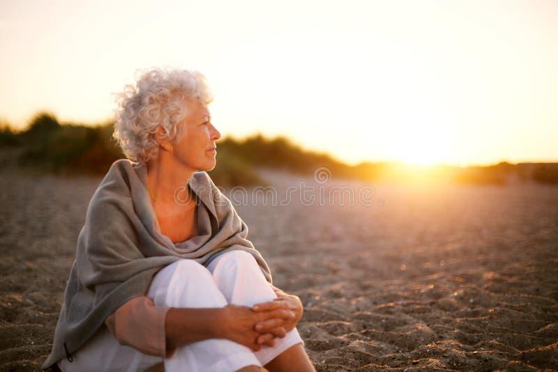 Alte Frau, die auf dem Strand weg betrachtet copyspace sitzt lizenzfreie stockbilder