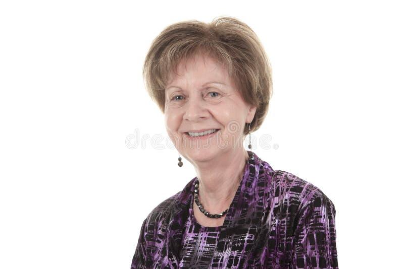 Alte Frau, die auf einem weißen Hintergrund lächelt stockfotografie