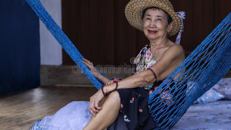 Alte Frau, die auf einer Hängematte sich entspannt lizenzfreie stockfotos