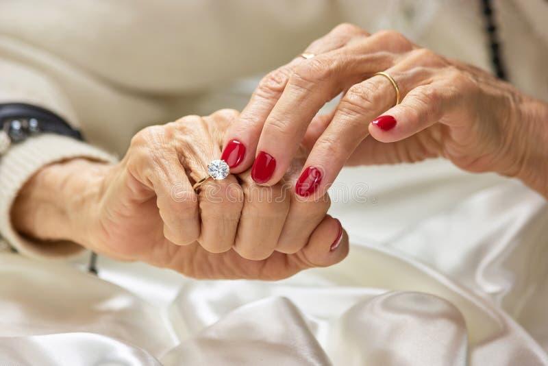 Alte Frau, die den Diamanten auf ihrem Finger berührt stockfoto