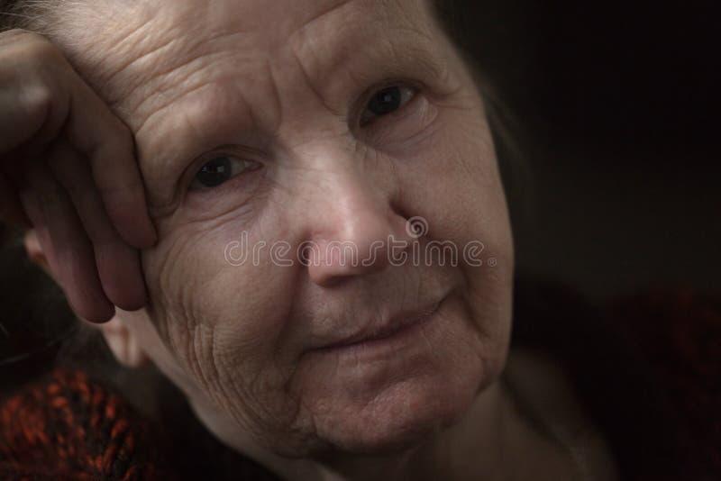 Alte Frau, die in der Dunkelheit denkt lizenzfreie stockbilder