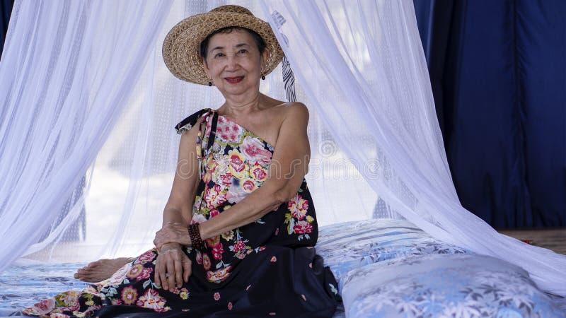 Alte Frau, die in einem Häuschen sich entspannt stockbild