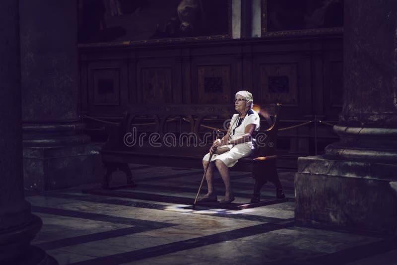 Alte Frau, die in farbigem Licht auf Kirchenbank sitzt stockbild