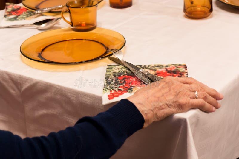 Alte Frau, die Hand auf Tabelle sitzt und hält stockfotografie
