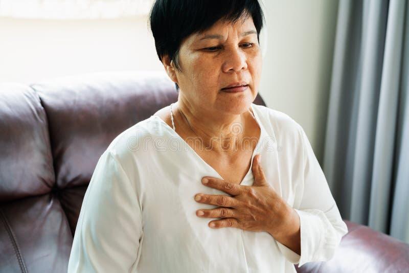 Alte Frau, die Herzinfarkt hat und ihren Kasten ergreift stockbild