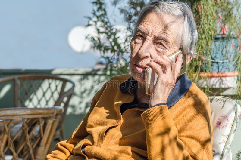 Alte Frau, die im Balkon spricht an ihrem Handy sitzt stockfotos